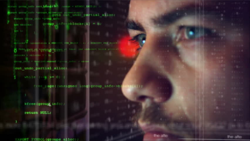 Male hacker working on a computer for cyber attack while green binary hacking code characters reflect on his face in a dark office room - industry 4.0 concept