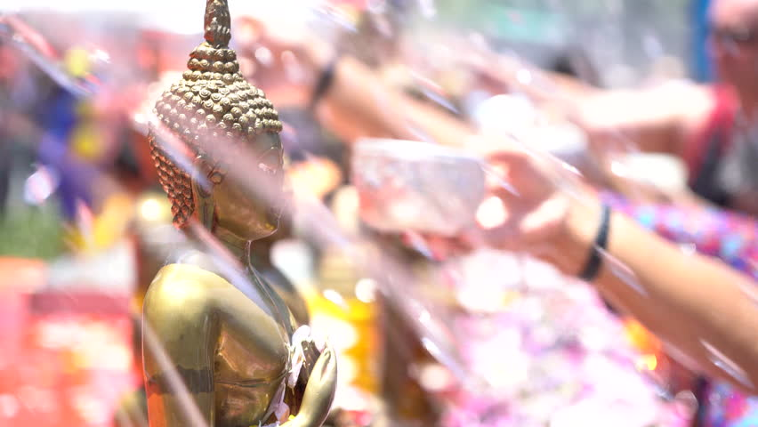 Slow motion Shower the monk sculpture with Songkran festival Thailand