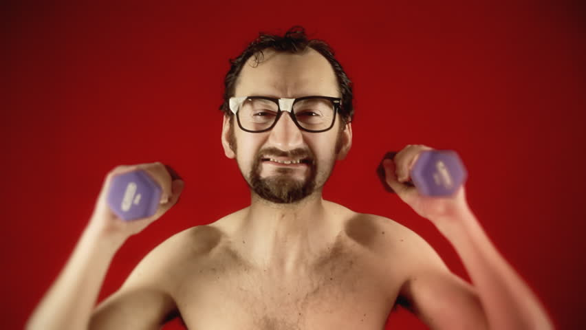 A funny ugly slim nerd man, exercising his arms with some weights, disappearing because of the excessive effort.   Shutterstock HD Video #26978188