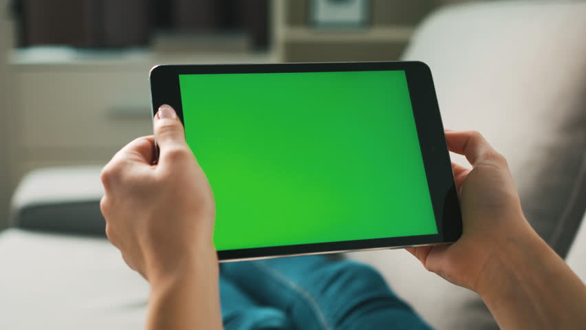 Woman hands using black tablet with green screen, lieng on sofa at home. View from the back. Chroma key. Close up. | Shutterstock HD Video #26988841