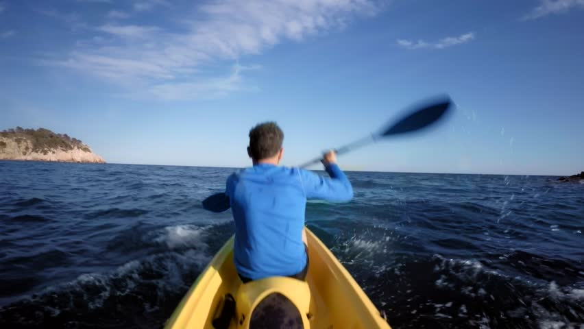 POV of passenger or sports activity partner from kayak in the middle of blue choppy water, sitting in the middle of yellow adventure kayak boat and paddeling together with a man in blue active wear