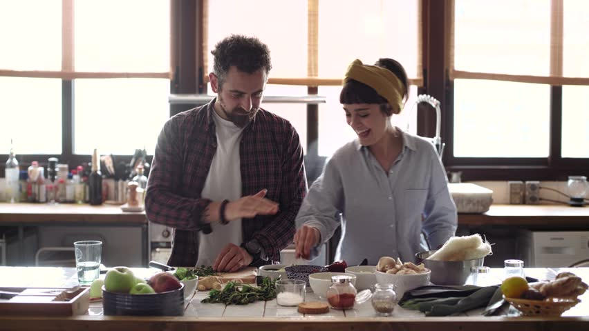 Funny happy couple cook dinner in an open space kitchen full of light, he is serious chops organic vegetables and she tries to steal a snack. they are excited, peaceful and loving #26995495