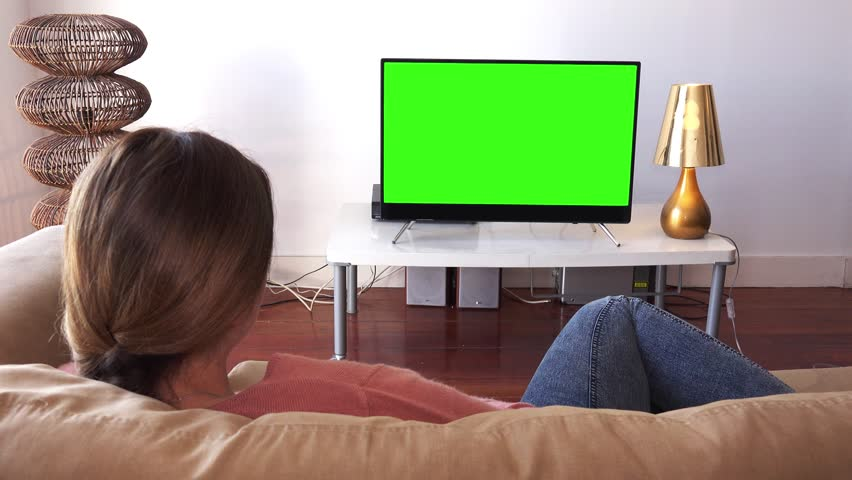 Young Woman Relaxed At Home Watching TV. Girl watching green screen television lying down on the couch | Shutterstock HD Video #26997223
