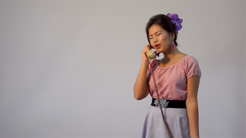 Asian woman in vintage style fashion, having an angry conversation on the phone - tracking shot.