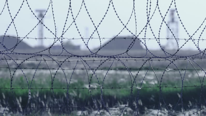 Barbed wire. Selective focus of barbed wire at airport with radar antennas in the background.