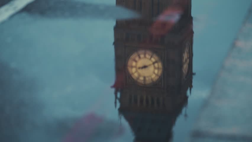 A reflection of Big Ben and double decker buses passing by on the puddle during a rainy night in London. | Shutterstock HD Video #27041764