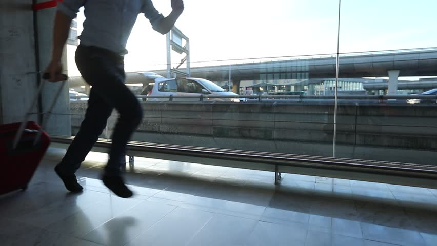 businessman running in slow motion to catch the flight in airport