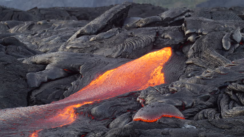 Surface flow lava oozes out of the nooks and crannies dried lava during an eruption from Kilauea volcano. | Shutterstock HD Video #27045658