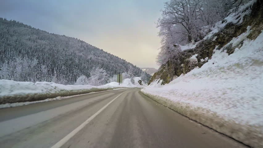 POV vehicle drive across beautiful countryside landscape with mountains range, winter snow, wet curvy road, forest trees and cloudy sky, car travel point of view | Shutterstock HD Video #27056761
