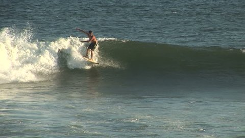 SALVADOR, BRAZIL - April 2008: Surfer rides a wave in Salvador, Brazil