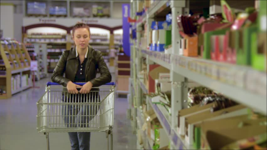Girl walks along wholesale shelves and taking goods in shop trolley, beautiful young wife shopping in a supermarket | Shutterstock HD Video #27058642