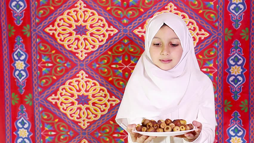 Little Muslim girl presenting a dish of dates for iftar - breaking fast in Holy Ramadan in front of islamic fabric background - showing generosity of Ramadan
