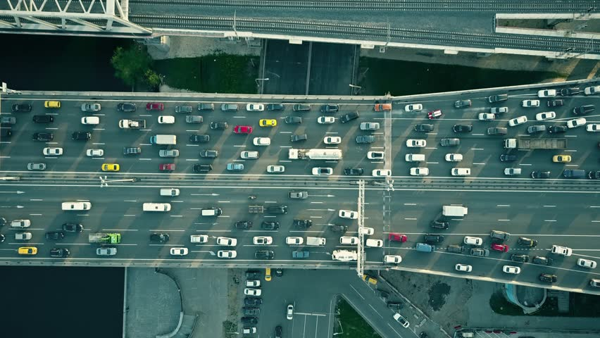 Aerial top down view of traffic jam on a car bridge and moving train. 4K video
