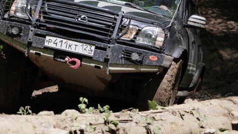 RUSSIA, ADYGEA, MEZMAI - MAY 8, 2017: Expeditionary jeep rides through the mud in the woods. SUV tries overcome the ditch with fast speed and jump.