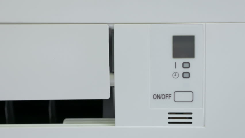 Wall mounted split air conditioner turning on. Closeup of indoor unit.