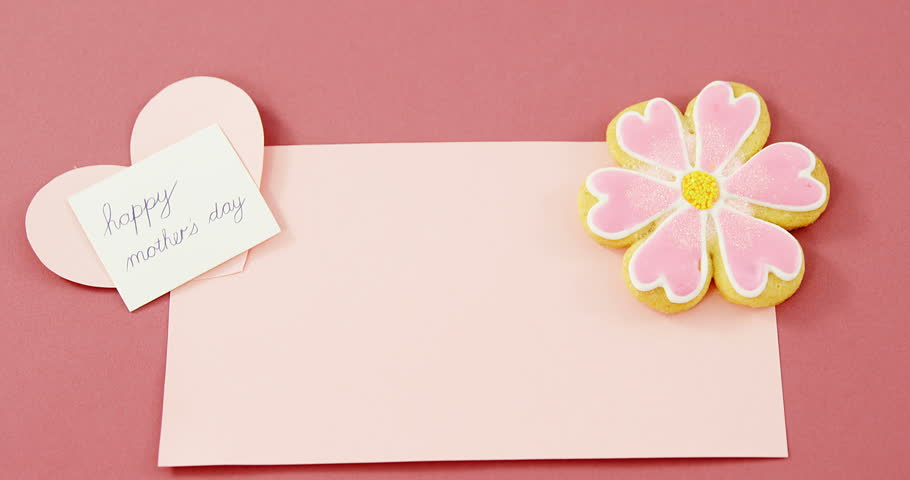 Close-up of flower shape cookie, heart shape card on red envelope against pink background #27092494