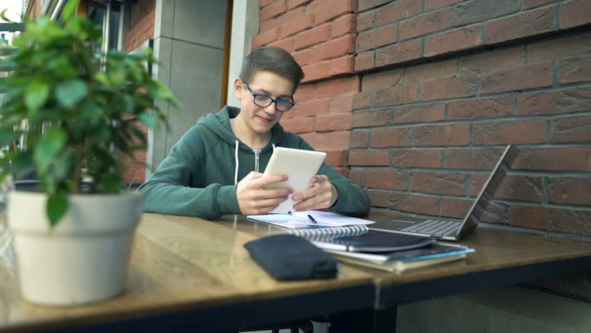 Young boy using tablet while studying in cafe in city  | Shutterstock HD Video #27095848