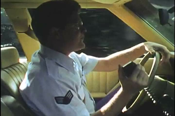 1980s: A United States Air Force serviceman drives a car, sings and takes a call on his radio, overseas, in 1986. | Shutterstock HD Video #27111337