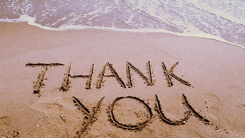 Thank you handwritten in sand on a beach.