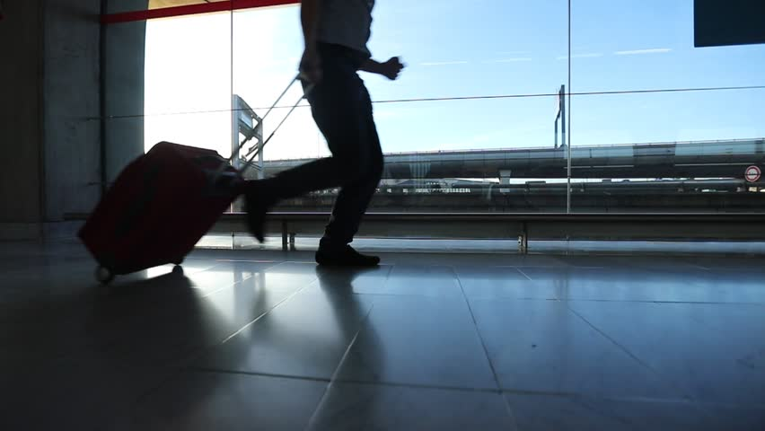 Slow motion of business man traveler running in hurry in the airport, silhouette of legs and baggage of passenger