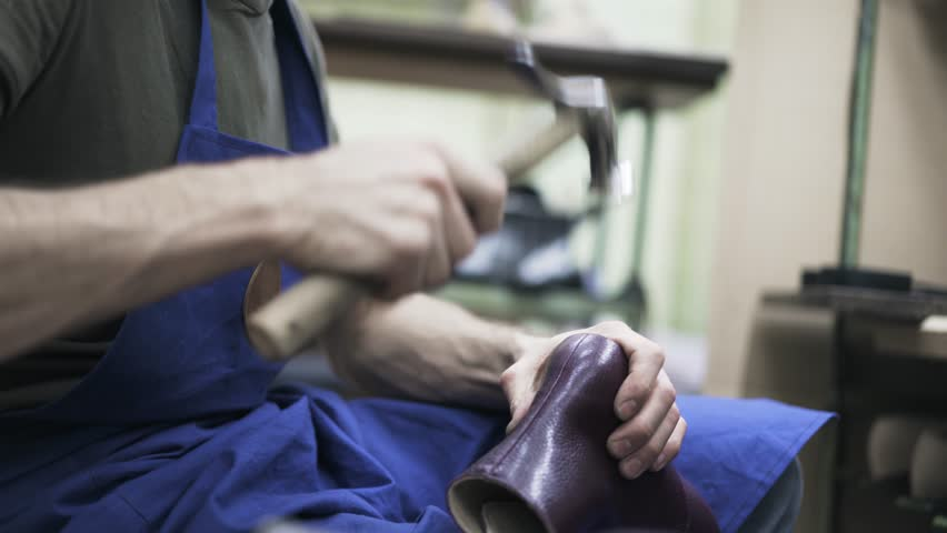Side view of a cobbler in a blue apron and a T shirt hammering a purple woman s boot. Handheld real time medium shot | Shutterstock HD Video #27122170