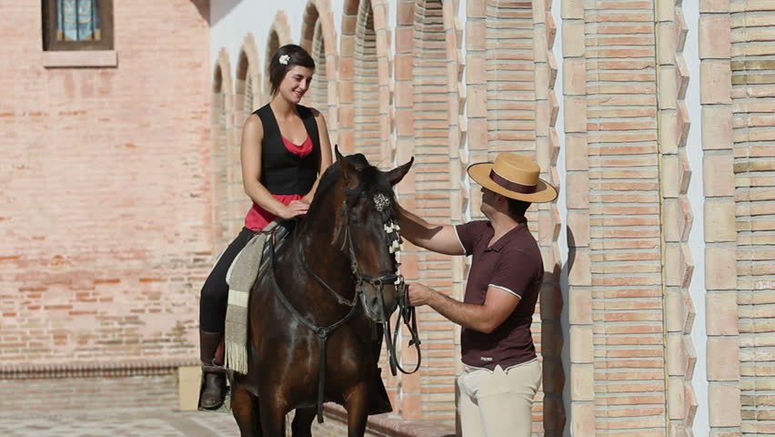 Man chatting to a woman on horseback in a village in Andalusia, Spain   Shutterstock HD Video #2714390
