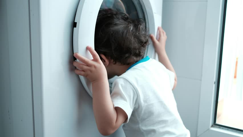 baby two years old boy looking washing machine at home in spin washing program. Home appliances issues.