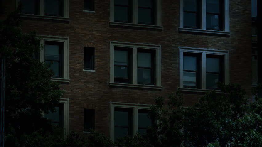 """A typical New York style apartment or office building establishing shot at night with the lights from a window turning on then off. Simulated """"day-for-night"""" composite. Day Matching ID: 10127561"""