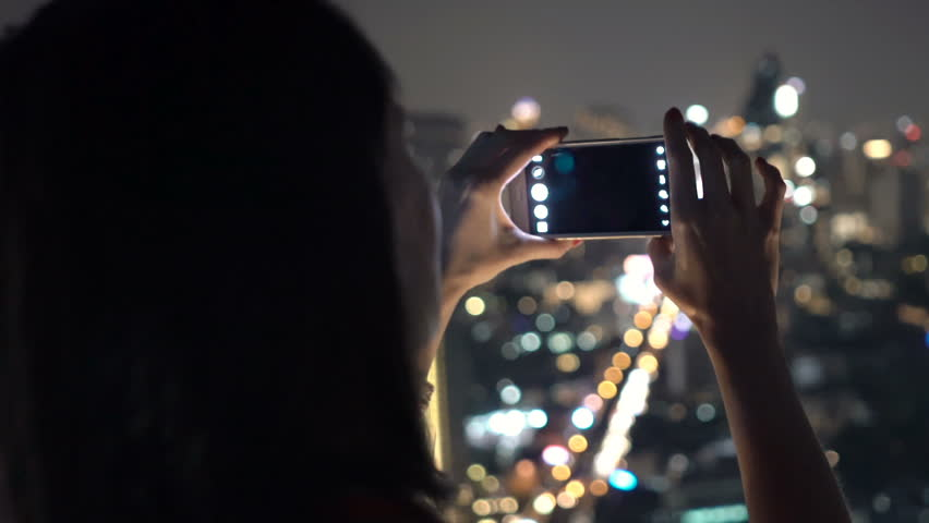 Woman taking photo of cityscape view with cellphone in bar at night   | Shutterstock HD Video #27179560