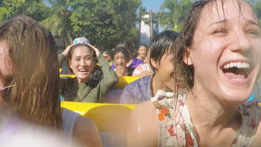 Thailand, Bangkok, 24 november 2015. Cheerful happy laughing girls riding at amusement water theme park enjoying splashing water. 1920x1080