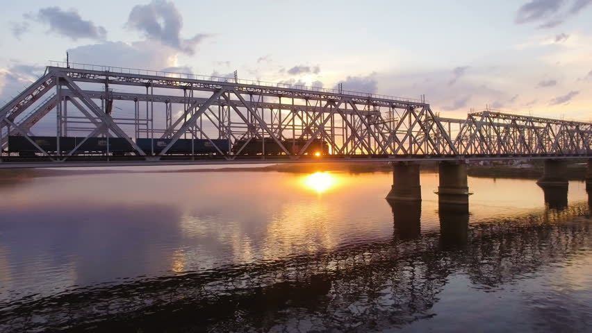 Railway bridge across the Volga river, which goes to a freight train. Aerial view