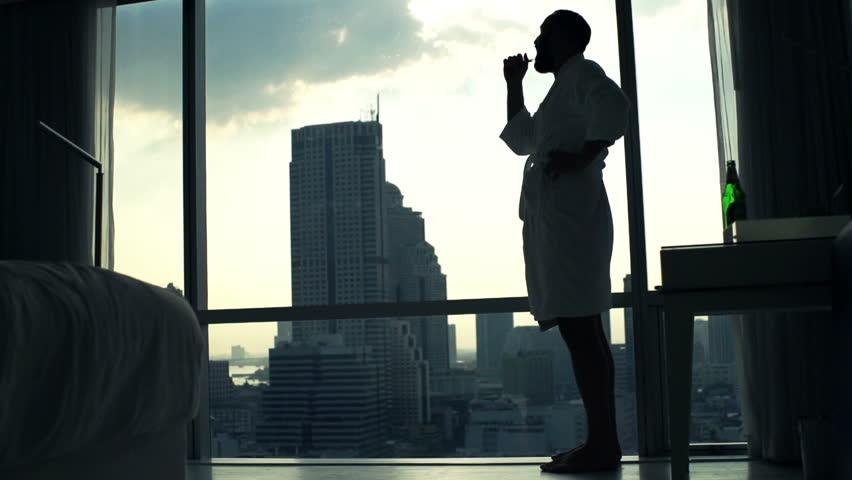 Man in bathrobe brushing his teeth by window at home  #27217270