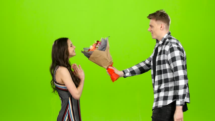 Guy is waiting for his girlfriend with a bouquet of flowers, she comes he gives flowers. Green screen