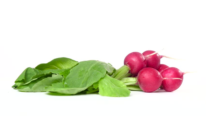 Bunches of freshly cut radishes are spinning on a white pinwheel. White background | Shutterstock HD Video #27228601