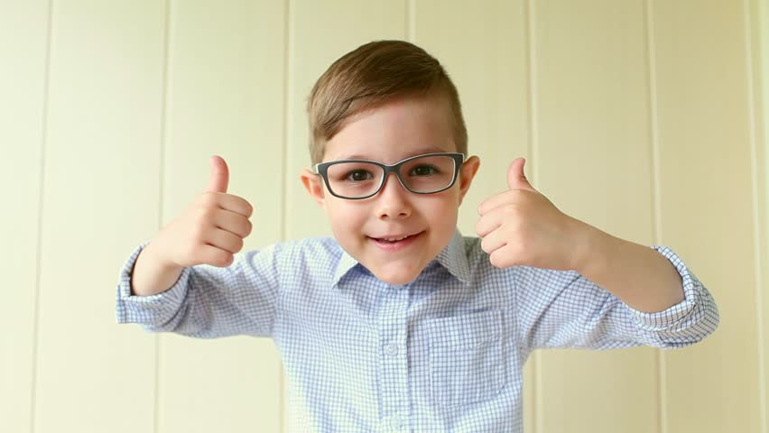 A child with glasses gives a thumbs-up. A kid likes the glasses. Little boy approves. | Shutterstock HD Video #27232747