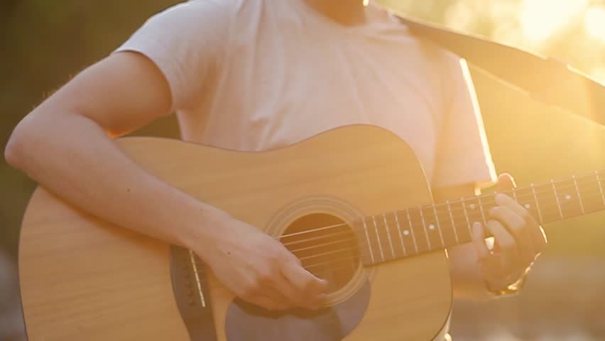 Close up of hands playing the guitar in the beautiful sunset slow motion