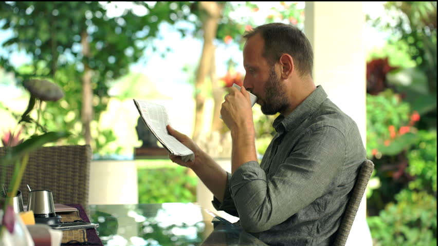 Young man reading newspaper and drinking tea sitting in the garden  | Shutterstock HD Video #27237694