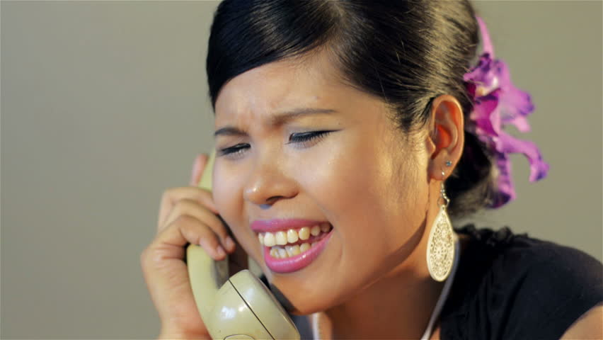 Young Asian woman answering the phone, getting mad and angry with a telemarketer, and hanging up in anger - tracking shot moving into focus.