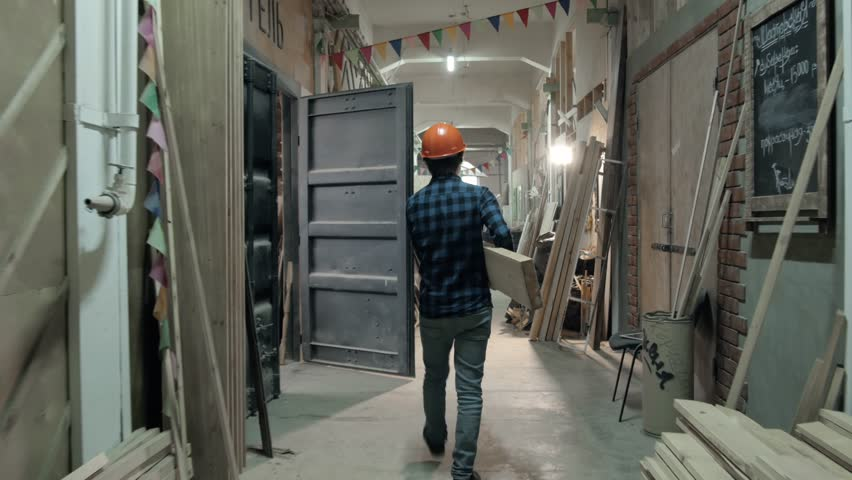Carpenter doing his job in carpentry workshop. Man walking on factory with plywood, furniture manufacture #27247954