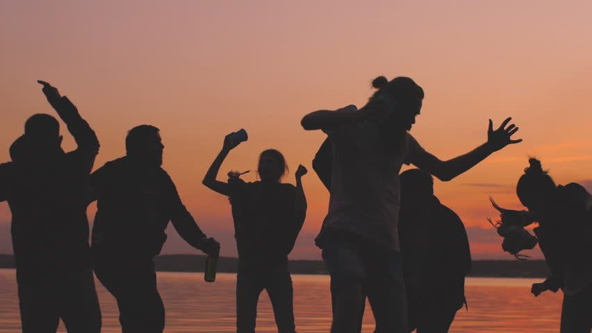 Slow motion of Silhouette group young dancing people have a party at beach on sunset