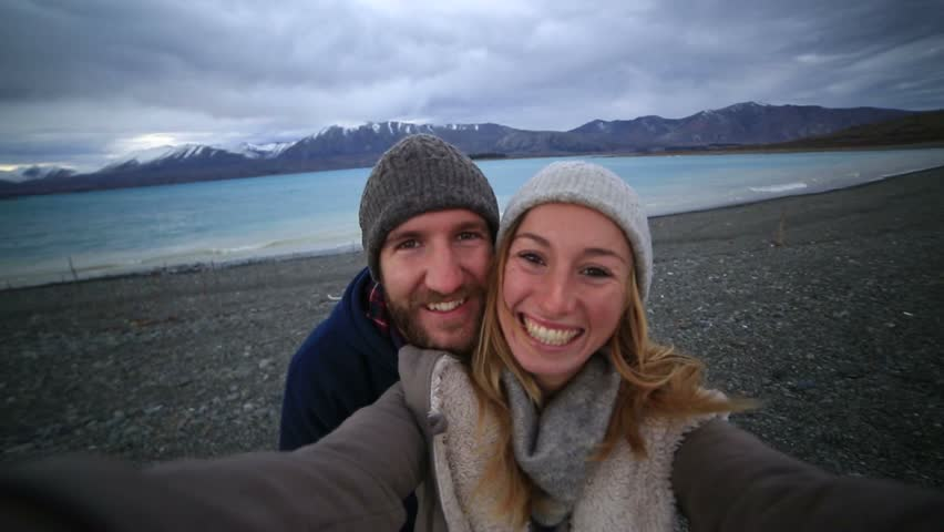 Young couple traveling take selfie portrait by the lake shore, New Zealand Young couple by the lakeshore take a selfie portrait with the spectacular landscape on the background.