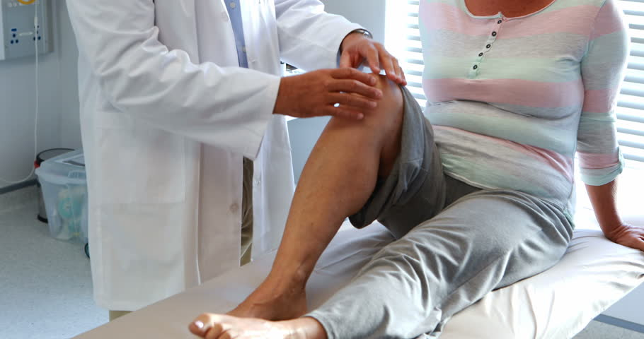 Physiotherapist giving knee therapy to senior woman in hospital