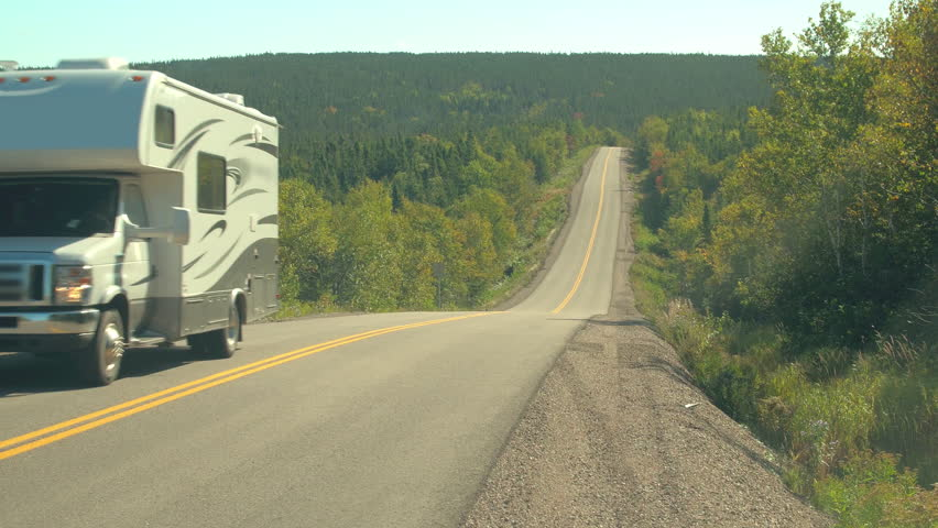 CLOSE UP: White camper car driving along empty highway in lush dense mixed forest covering the hills in the Canadian wilderness on sunny day. People on road trip in remote area in Nova Scotia, Canada