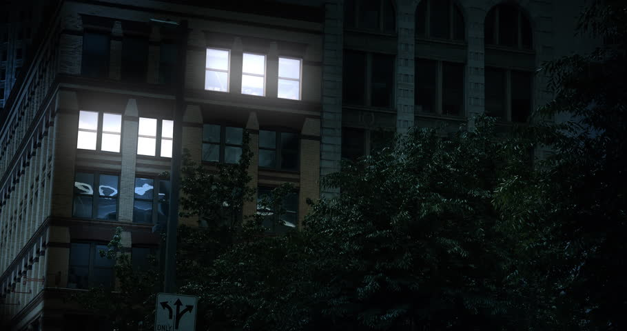 """A typical New York style apartment or office building establishing shot at night with the lights from a window turning on and off. Simulated """"day-for-night"""" composite."""