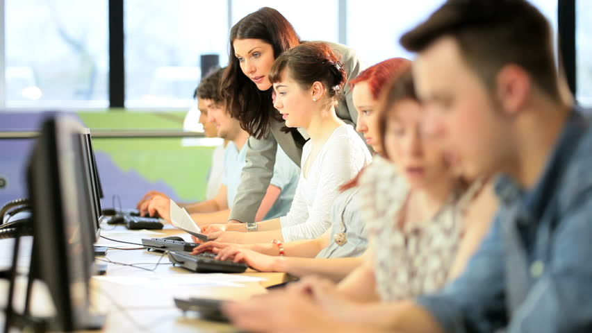 Female college lecturer teaching online young multi ethnic students in computer room