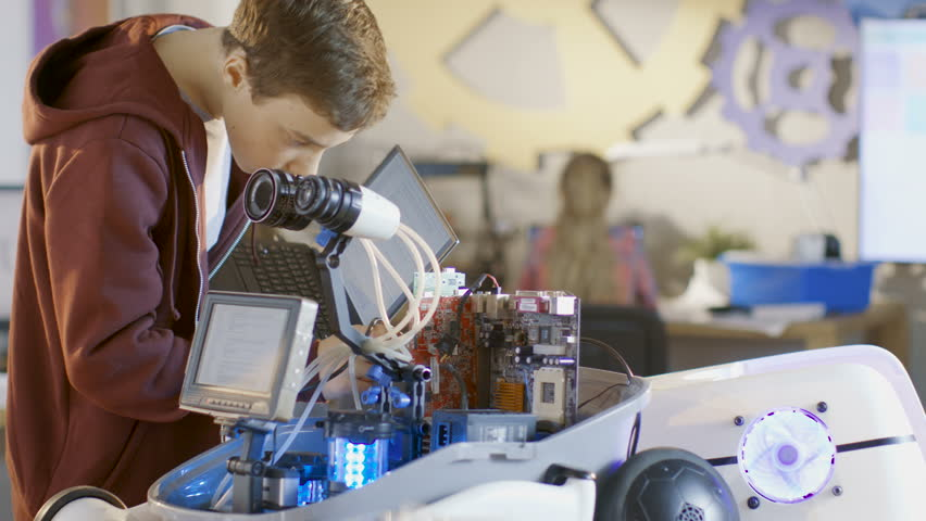 Boy Works on a Fully Functional Programable Robot with Bright LED Lights for His School Robotics Club Project. Shot on RED EPIC-W 8K Helium Cinema Camera. #27304609
