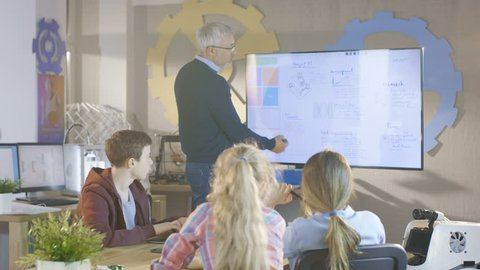 Teacher Explains Lesson To His Computer Science Class. He uses Interactive Whiteboard. Shot on RED EPIC-W 8K Helium Cinema Camera.
