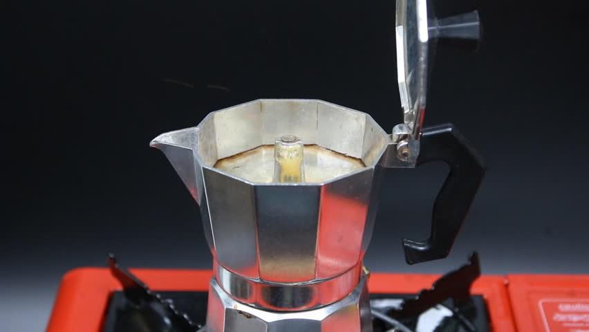 Moka Pot coffee maker on orange stove and a black background. finish with smoke.   Shutterstock HD Video #27305017