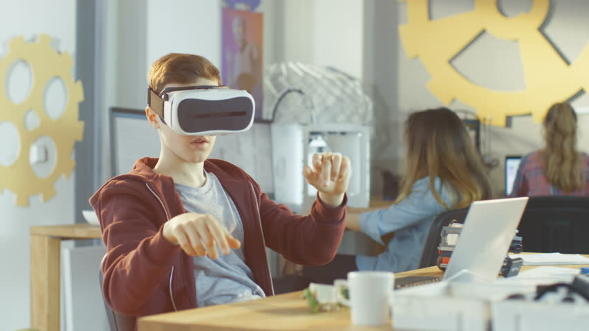 In a Computer Science Class Boy Wearing Virtual Reality Headset Works on Programing Gestures for the Project. Shot on RED EPIC-W 8K Helium Cinema Camera. | Shutterstock HD Video #27315670