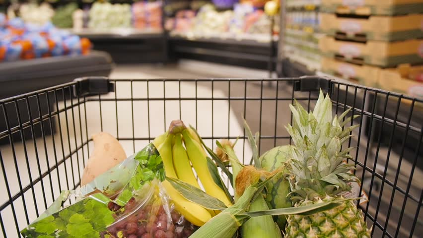 Slow-motion clip of a half-filled shopping cart moving through the produce aisle. Inside the cart, several kinds of fruits such as bananas, pineapple, watermelon, and grapes can be seen.